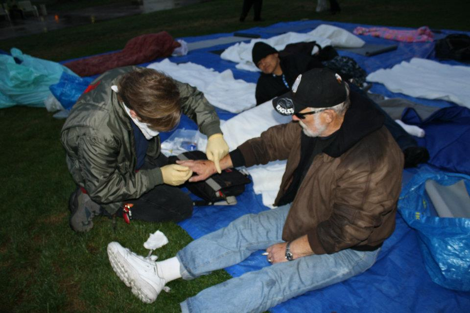 Medic gives homeless man first aid at Necessity Village