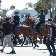 MINOR SCUFFLE: An Anaheim Police officer and an Orange County Sheriff's Deputy, both mounted on horseback, use long sticks to prod anti-police brutality protesters off the streets and onto the sidewalks...
