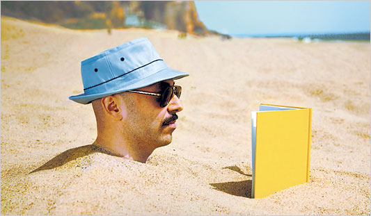 Man reading while buried in sand up to the neck