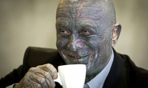 Facially tattooed man drinking coffee