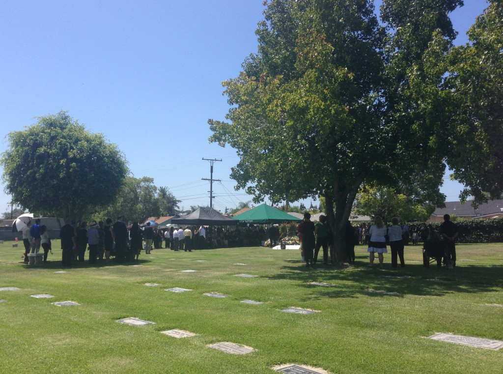 Long shot of Hoagy's mourners near the tent, and some under the shade trees.