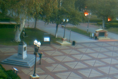 In a shot from the campus webcam, Dec. 1 at 7:05 a.m., a man in a teal coat apparently offers a small child as a blood sacrifice to Tommy Trojan in the hope of securing divine aid to defeat Stanford in this weekend's Pac-10 Championship game.  OJB doubts that even that would work.  In any event, we're not even entirely convinced that he's holding up a child at all.  The ways of USC are mysterious to us.