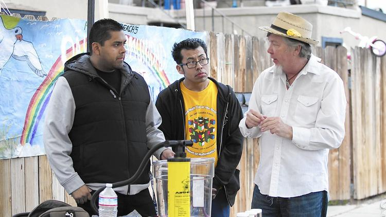 Denny Larson, right, an environmental expert, shows residents of the Oak View community how to build and operate a self-made air pump during a meeting on Friday in Huntington Beach. (Don Leach / Huntington Beach Independent)